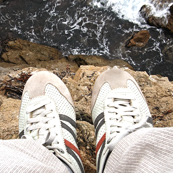Looking down upon shoes over a cliff